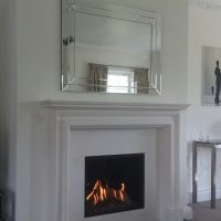 White fireplace mantle beneath a mirror in a Surrey living room