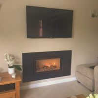 A Fireplace in a living room below a TV